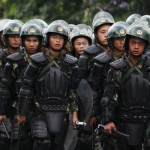 Riot police patrol on a street in the township of Xintang in Zengcheng near the southern Chinese city of Guangzhou